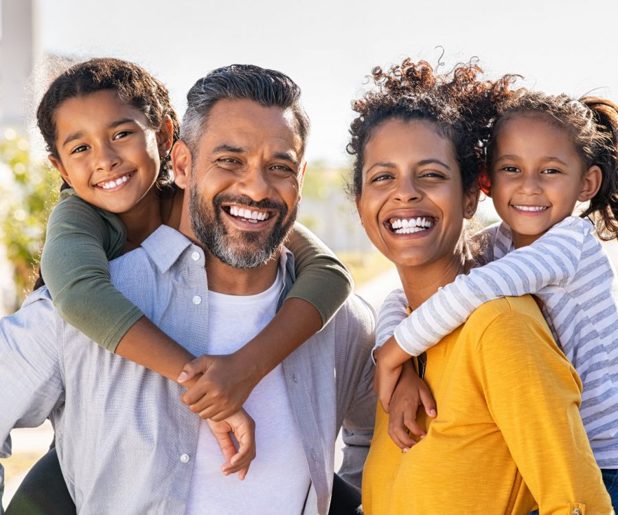 Mixed race parents giving piggyback ride to their children outdoor. Portrait of happy african mother and indian father with daughters looking at camera outside house. Smiling and joyful family standing with their beautiful little girls.